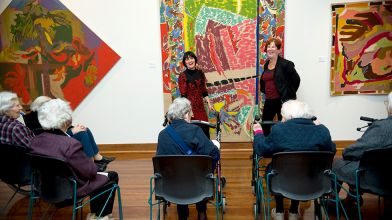 Art and Dementia session facilitators engaging audience with the exhibition Man for All Seasons: Rollin Schlicht