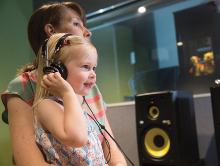 A child with headphones on, in a studio with her mother