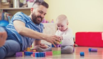 Dad and infant stacking blocks