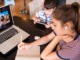 Two children doing school work at home