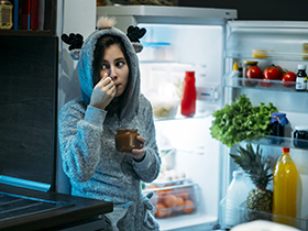 A teen eating something from an open fridge