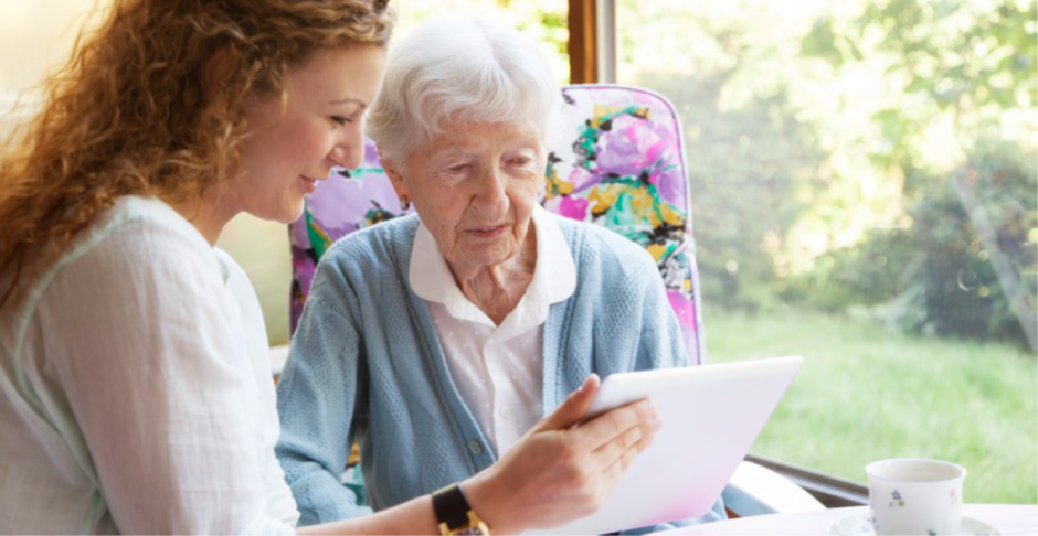 A woman holds up a tablet computer to show an elderly woman.