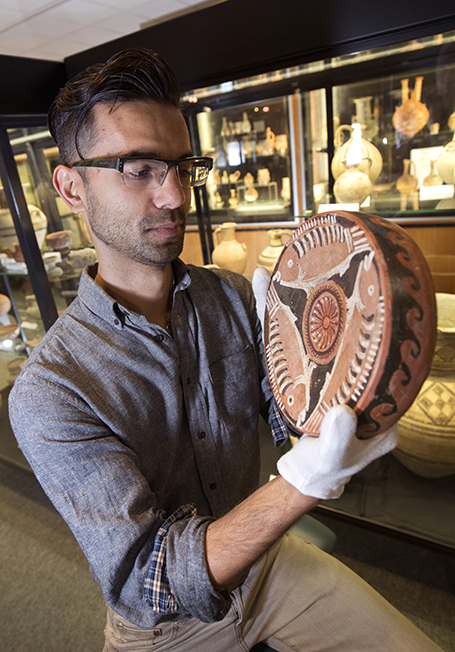 A Macquarie student obverves an ancient vase in the Museum of Ancient Cultures.