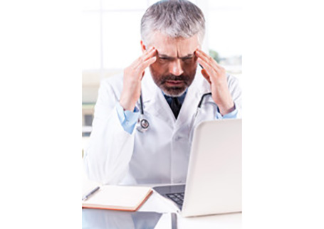 A doctor frowning in front of his laptop