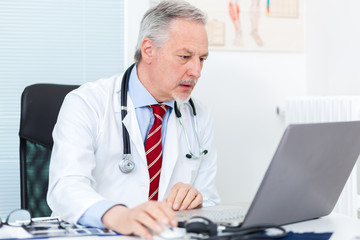 A doctor looking at his laptop