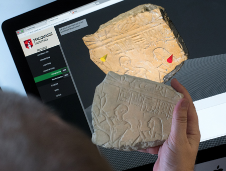 Comparing a piece of pottery with the image on a laptop