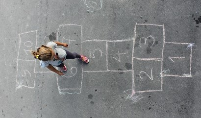 image of little girl playing hopscotch