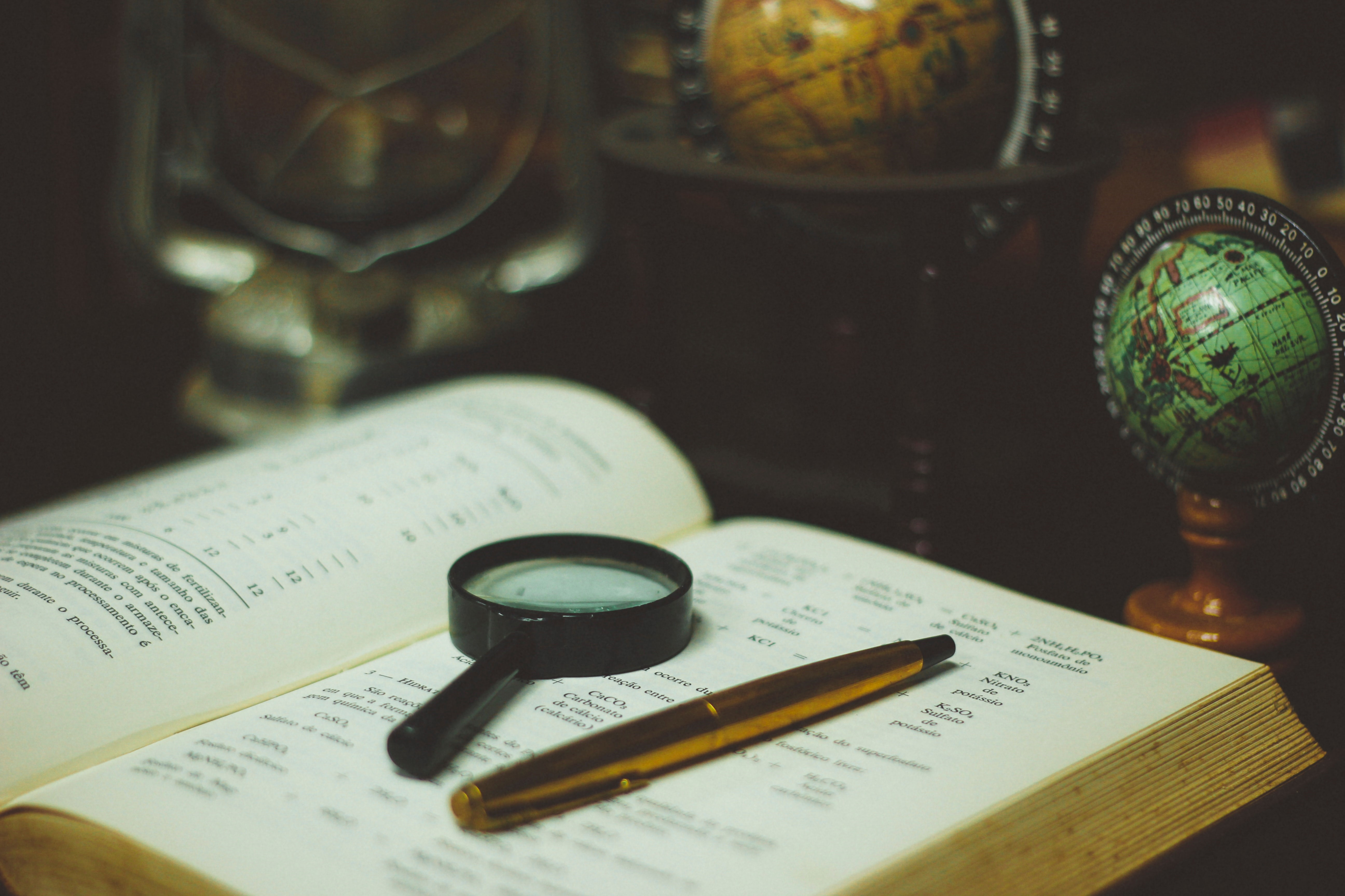 Open book with magnifying glass and pen