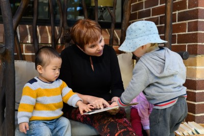 An early childhood educator reads a book with two young children