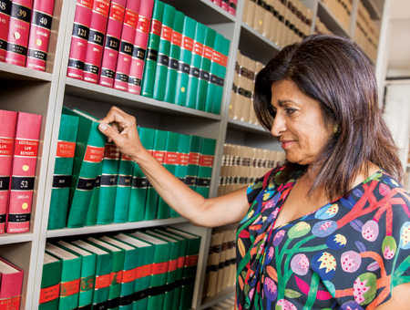 A woman looking through legal text books