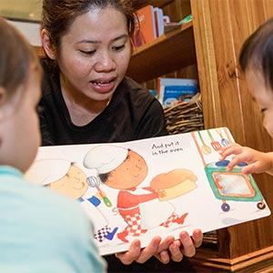 teacher showing picture book to children